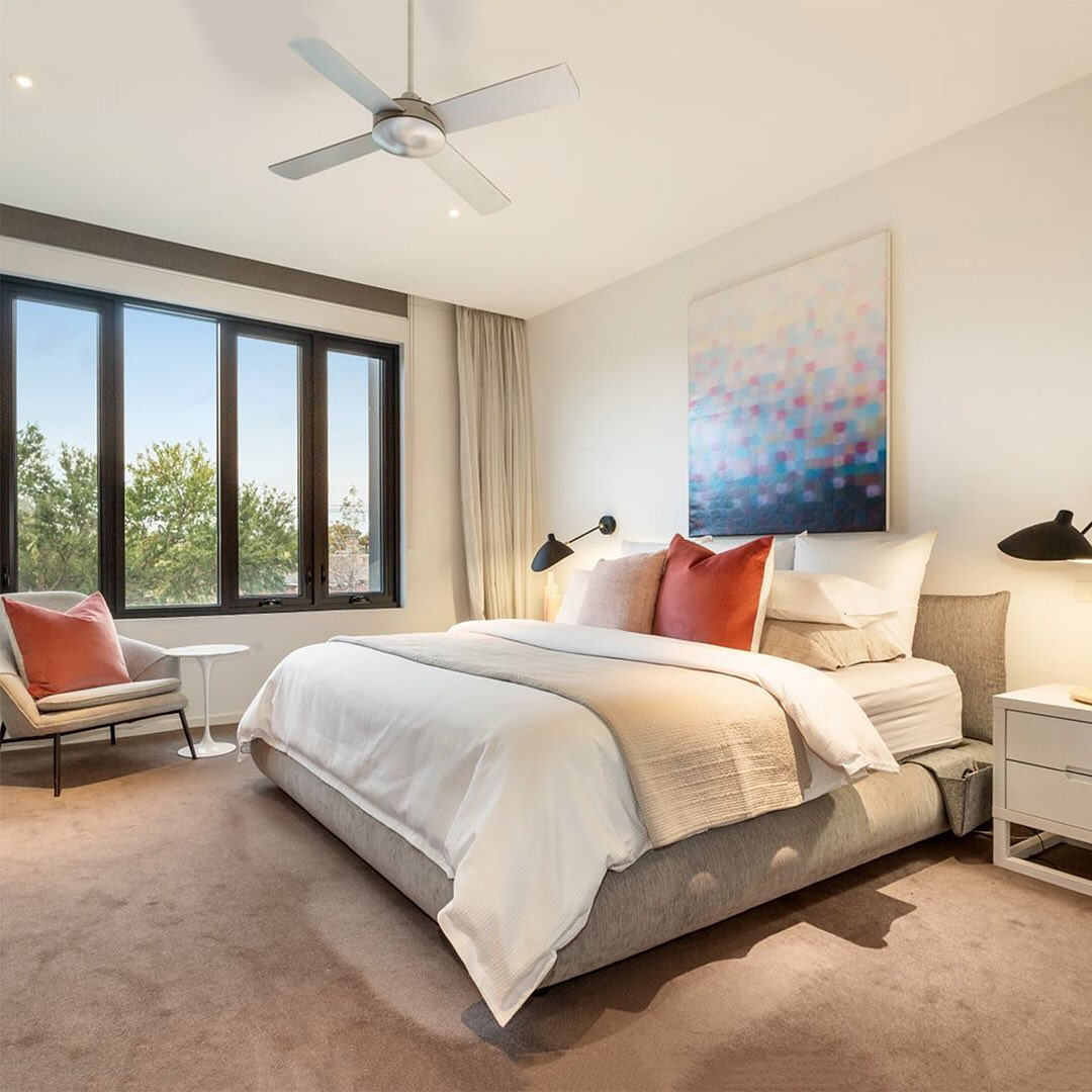 a lofty master bedroom contains a neutral color palette of